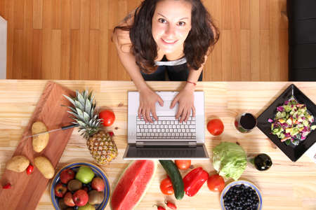 A young woman using a Laptop while cooking  Foto de archivo