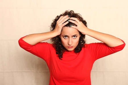 A worried woman holding her head