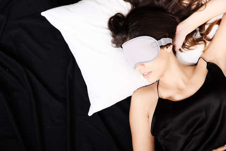 A young woman sleeping with a eye covering mask  photo