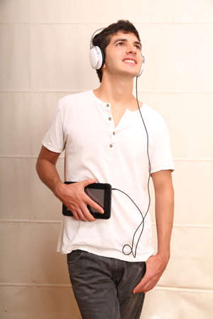 A young, latin man with a Tablet PC and headphones photo
