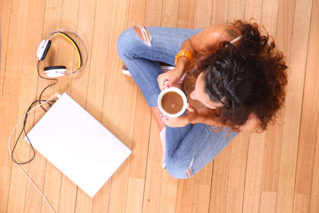 A girl sitting on the floor with a Laptop and some coffee. photo
