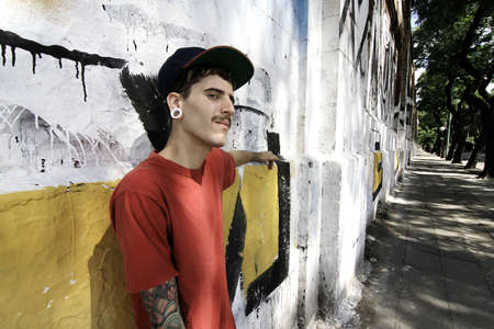 A young Rapper leaning against a wall. photo