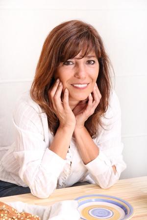 Portret van een mooie volwassen vrouw zitten in de keuken. Stockfoto
