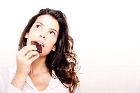 Portrait of a beautiful, latin Woman eating chocolate