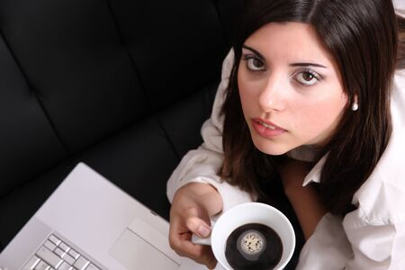 A young, hispanic adult girl watching a Laptop while drinking coffee. Stock Photo - 22813105