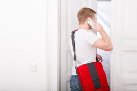 Een jonge en drukke student thuiskomen tijdens het gesprek op de smartphone. Stockfoto