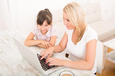 Een moeder met haar dochter te kijken naar een laptop thuis. Stockfoto