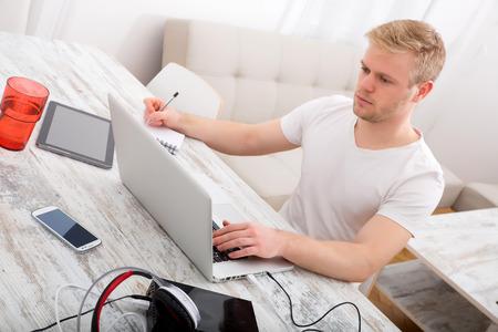 Een jonge blanke man aan het werk in zijn kantoor aan huis.