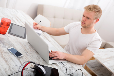 A young caucasian man working in his home office.