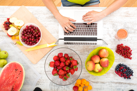 A beautiful mature woman using a Laptop computer in the kitchen with fruits.
