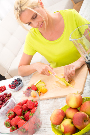 A beautiful mature woman preparing a smoothie or juice with fruits in the kitchen. photo