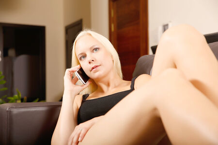 A blonde girl talking with a smartphone. photo
