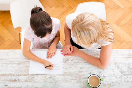 A mother helping her daughter with the homework seen from above. Banque d'images