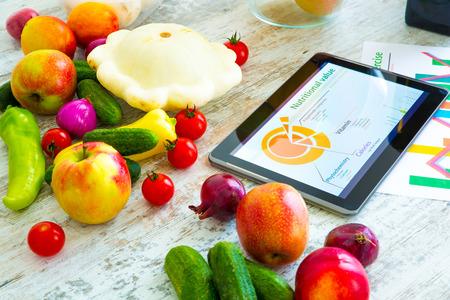Biologisch voedsel en een Tablet PC met informatie over gezonde voeding en fytochemische samenstelling. Stockfoto