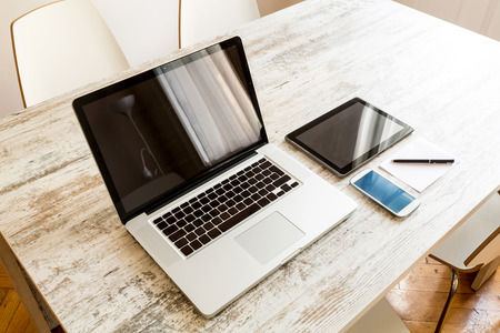 A Laptop computer, a Tablet PC and a Smartphone on a Desktop. Stockfoto