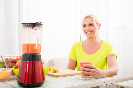 A beautiful mature woman enjoying a smoothie or juice with fruits in the kitchen. Reklamní fotografie - 33706182