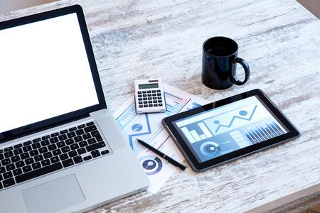 Business Analytics op een houten bureau met een tablet-pc en een laptop.