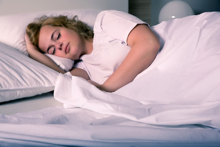 A plus size young woman sleeping in bed at night.