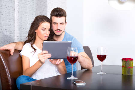 A young couple using a Tablet PC while having a glass of wine at home.