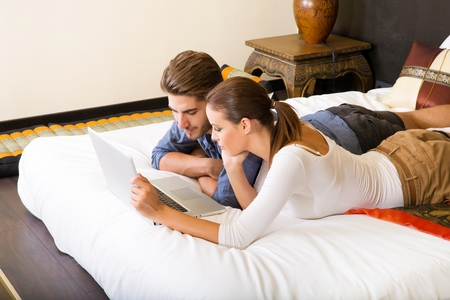 Young couple using a tablet pc in their hotel room