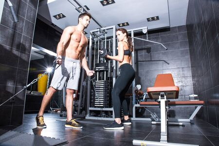 A young couple training together in the Gym. Reklamní fotografie