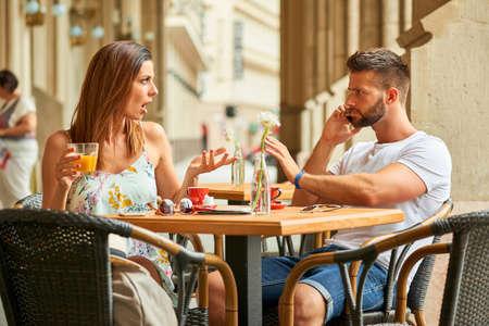 Una bella giovane donna è sconvolto per il suo bel fidanzato perché lui sta parlando al telefono mentre stanno avendo un caffè a un tavolo su una terrazza a Budapest, Ungheria.