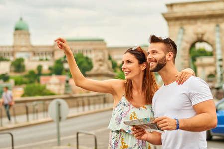 Een mooie jonge vrouw weg te wijzen tijdens haar vriendje houdt een kaart met het kasteel van Buda en de Kettingbrug achter hen in Boedapest, Hongarije.