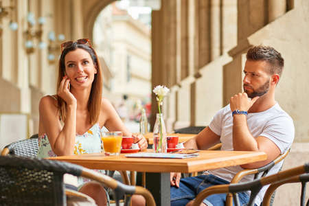 Un bel ragazzo è sconvolto per la sua bella fidanzata, perché lei sta parlando al telefono mentre stanno avendo un caffè a un tavolo su una terrazza a Budapest, Ungheria.