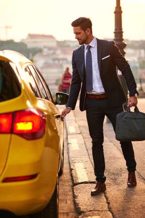 Een knappe jonge zakenman krijgt in een taxi in de zonsondergang