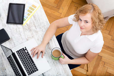 A plus size adult woman working in the home office. Stock Photo