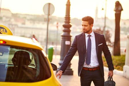 Jonge zakenman met een taxi