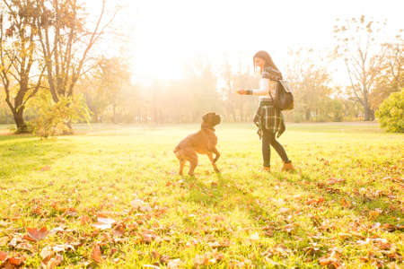 Beautiful young woman playing with her Dog in the forest