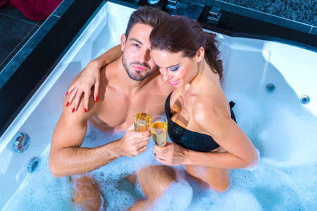 Beautiful young couple drinking Champagne in the Whirlpool