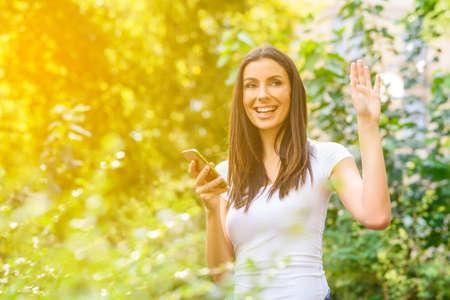 彼女のスマートフォンを使っている間に友人に挨拶する若い女性 写真素材