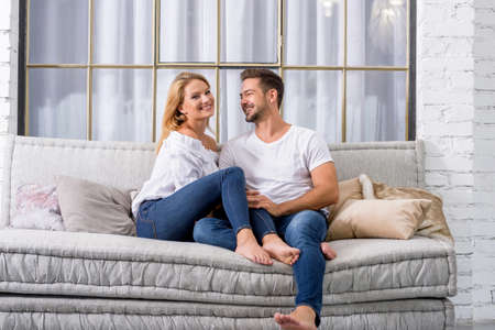 A beautiful young couple sitting on the sofa and cuddling. Archivio Fotografico