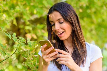 Une femme gaie dans un parc en utilisant son smartphone Banque d'images - 91007450