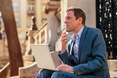 A middle age businessman siting on the stairs with a laptop and a phone in his hand and thinking