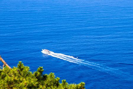 Aerial view of a boat cruising on the blue Mediterranean sea on a sunny day.
