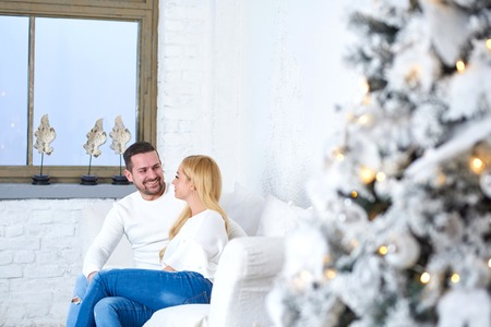 A beautiful happy young couple sitting on the sofa in the living room with the christmas tree.