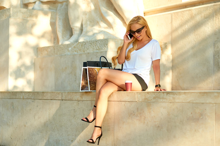 Young woman siting and talking on her phone