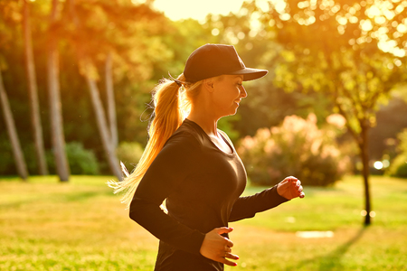 A beautiful young blonde woman wearing black clothes and baseball cap  while running in a park in the sunset Imagens