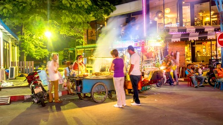 PATTAYA, THAILAND - CIRCA FEBRUARY 2018: View on people as they pass by at a Street Food Barbecue kitchen at night circa February 2018 in Pattaya, Thailand.