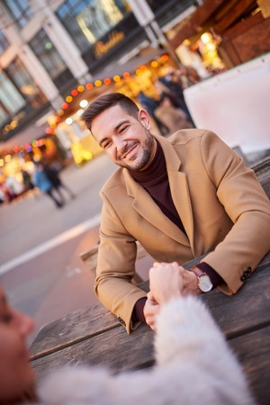 Portrait of a handsome young man while sitting in a christmas market and holding his girlfriends hand.
