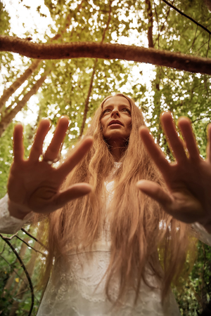 Dark mood photo of a woman while standing in the forest and showing her hands to the camera.