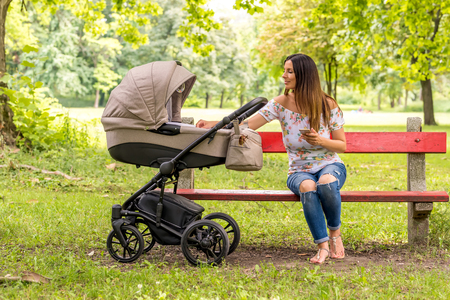 A young mother sitting on a bench in the park and checking her baby in a stroller while using her smartphone. Stock Photo