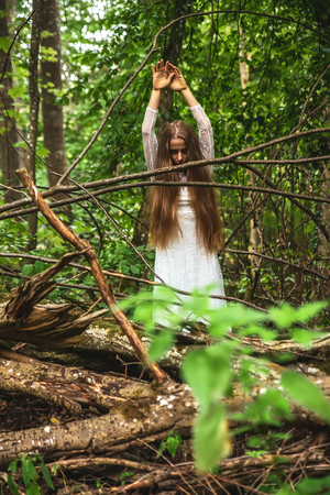 Dark mood photo of a woman while standing in the forest and reaching up with her hands.