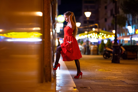 A beautiful mature woman in a red dress checking the storefront at night with the city lights in the background. Stock Photo