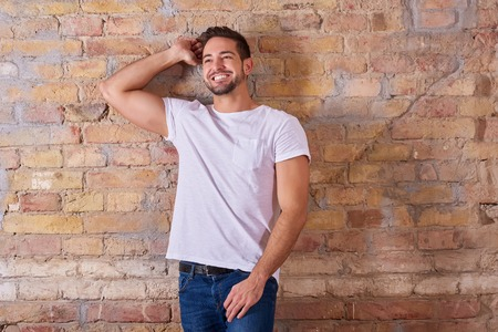Portrait of a happy handsome young man in a white tshirt. Reklamní fotografie