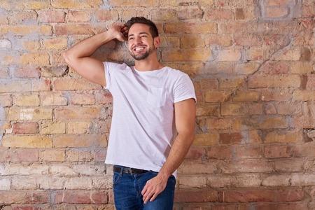 Retrato de un joven apuesto feliz con una camiseta blanca. Foto de archivo