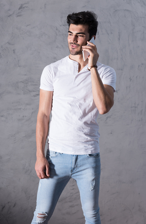A happy handsome young man in a white tshirt talking on his phone in front of a grey wall in a studio.